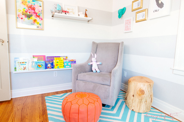 Modern Glider with Coral Pouf in this Reading Nook