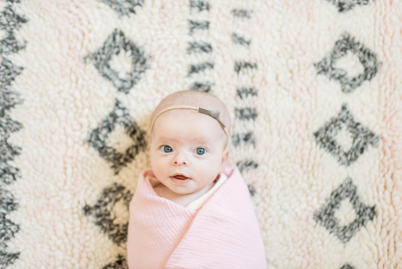 Swaddled Baby on Nursery Rug