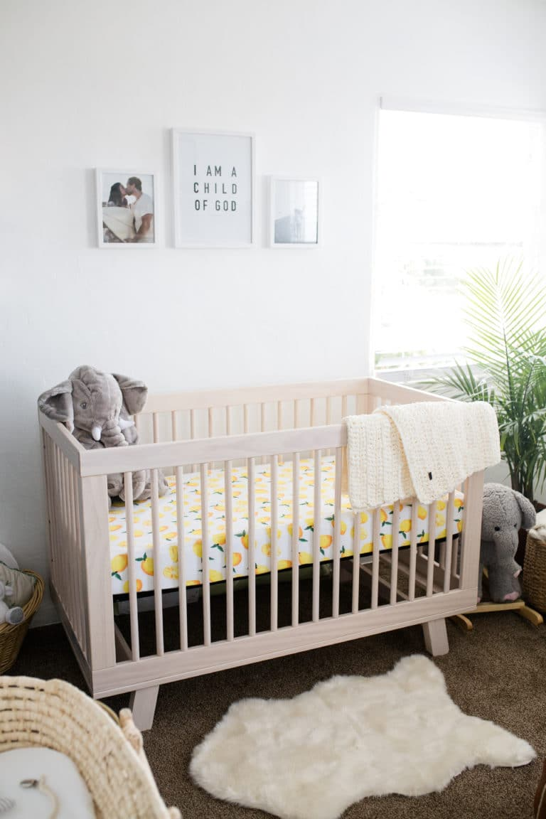 Modern Boho Nursery with a Punch of Tropics Natural Wood Crib with Lemon Sheet