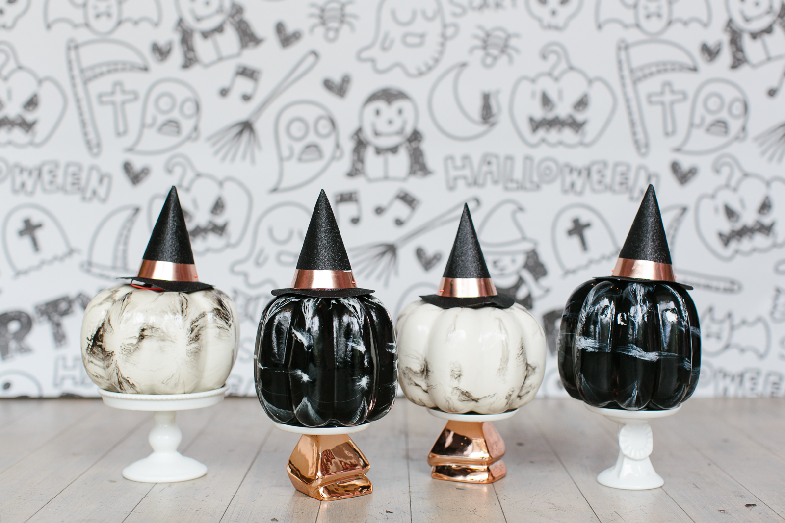 Black and white marble pumpkins with mini witch hats on top of cupcake stands