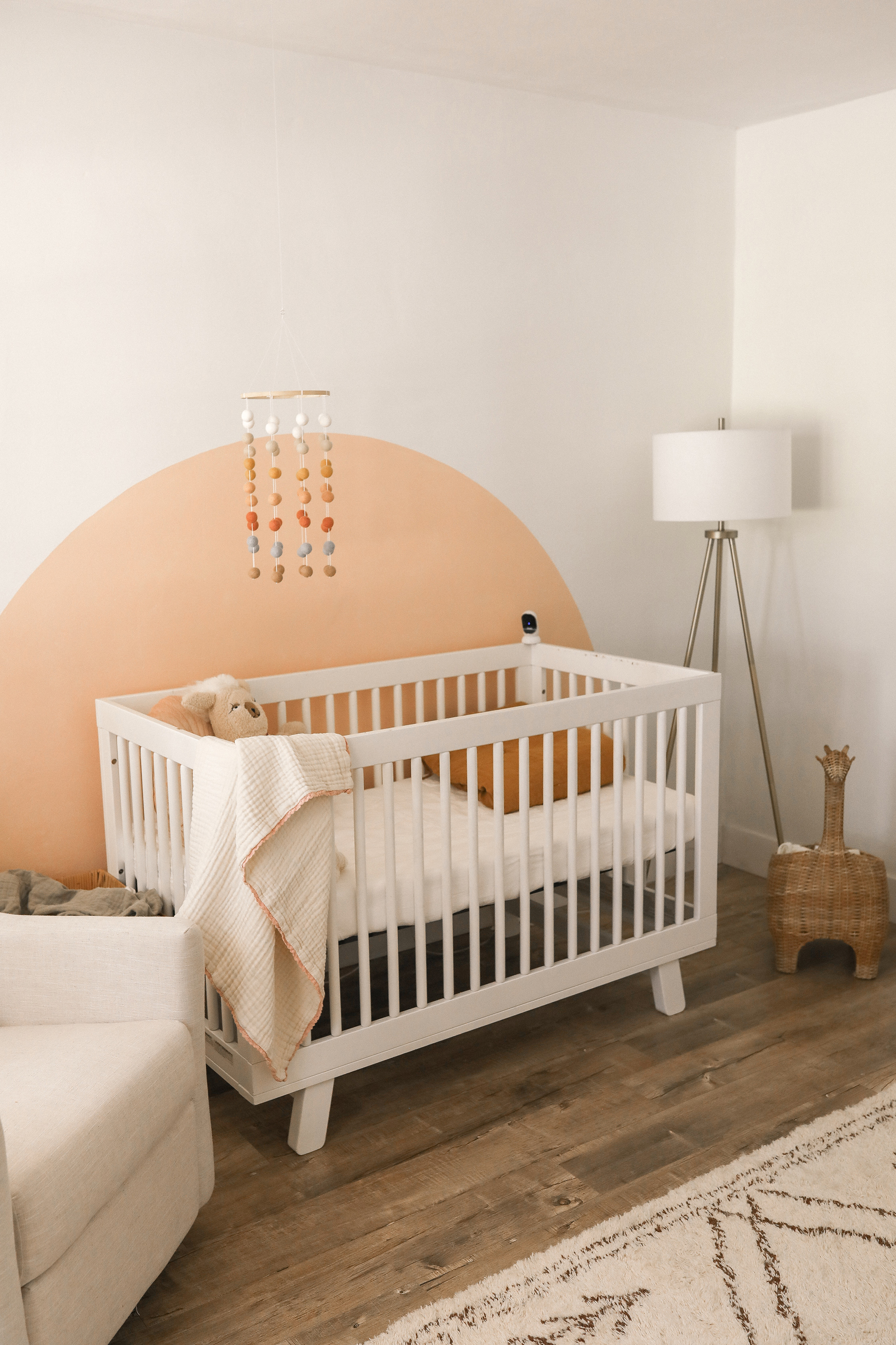 Peach Nursery with Painted Arch behind the Crib designed by Tayler Golden