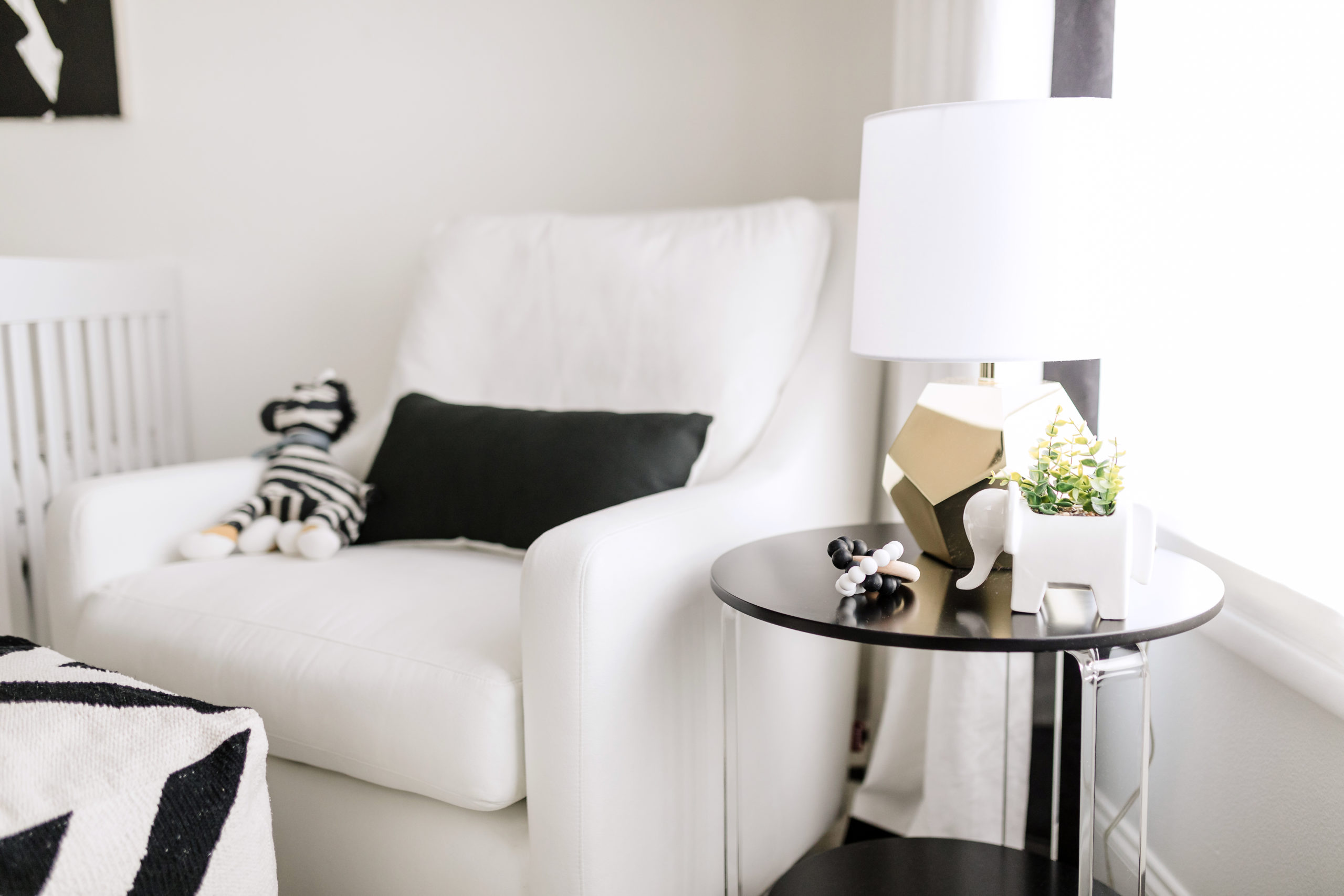 White Glider and Black Acrylic Side Table in Nursing Nook
